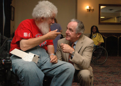 Sen. Harkin has a conversation with a man attending the American Association of People with Disabilities ADA Anniversary event in 2006.