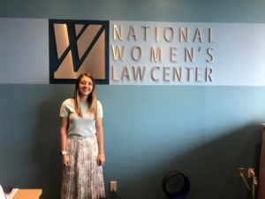 Sloan Nickel stands in front of a sign for the National Women's Law Center where she is completing an internship this summer.