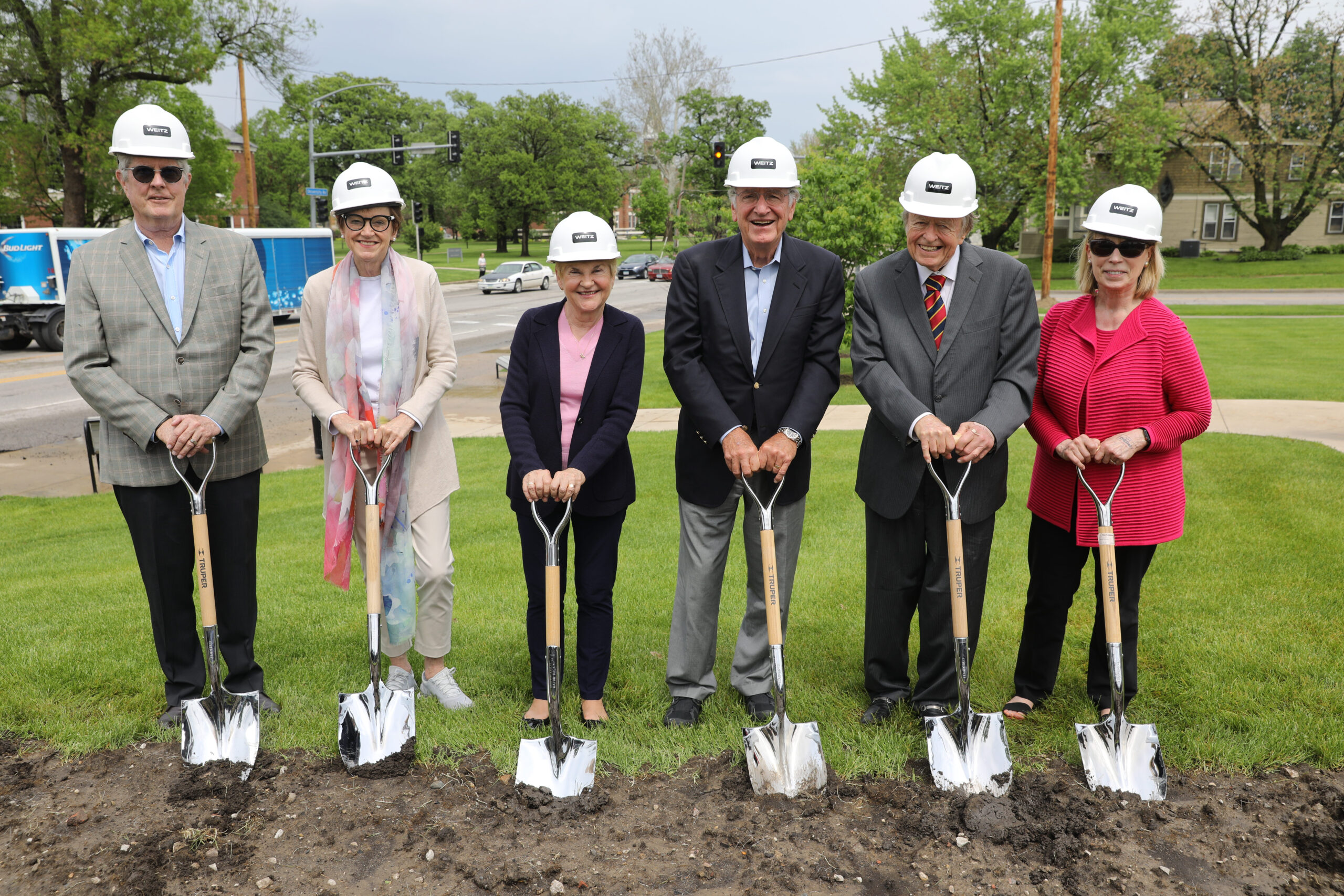 Six people wearing hard hats stand on a patch of dirt holding shovels.