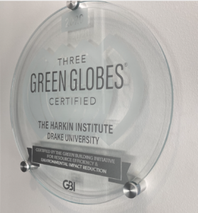 Circular plaque hanging in the entrance of the Tom and Ruth Harkin Center that reads: Three Green Globes Certified. The Harkin Institute. Drake University.